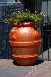 Large orange vase with tsfet on the sidewalk of the city.