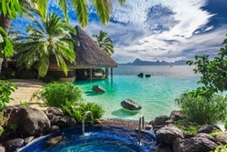 Large outdoor jacuzzi and infinity pool over tropical ocean, Tahiti resort