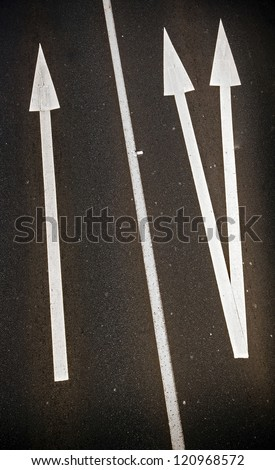 Large painted arrows on a freeway contrast with the bitumen for business concept - stock photo