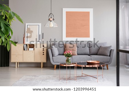 Large painting on a gray wall above an elegant sofa with cushions in a stylish living room interior with copper furniture #1203996451