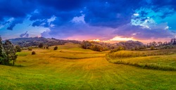 Large panorama of mountain village in summer evening. Sunset with dramatic sky. Forecast rain and wind. Agriculture field. Meadows and oak forest. Serbia, Europe.