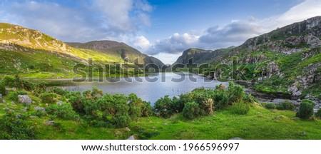 Large panorama with Black Lake valley and mountains at sunset in Gap of Dunloe, Black Valley, MacGillycuddys Reeks mountains, Ring of Kerry, Ireland Stok fotoğraf ©