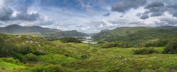Large panorama with Irish iconic viewpoint, Ladies View, with multiple lakes, green valley, forest and mountains, Killarney, Rink of Kerry, Ireland