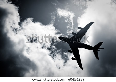 large passenger jet silhouette against a cloudy sky