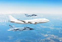 Large passenger plane, accompanied by two military fighter. Concept of airborne danger, air force