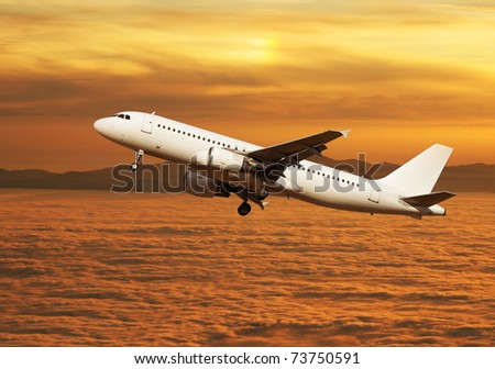 Large passenger plane flying over clouds at sunset