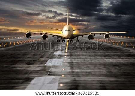 Large passenger plane runs along the airport runway during sunset time