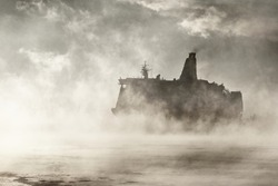 Large passenger ship (cruise liner) sailing near the coal terminal in a clouds of morning fog at sunrise. Riga bay, Baltic sea, Latvia. Epic seascape. Monochrome, atmospheric, concept image