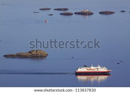 Large passenger ship sailing along scenic norwegian coast