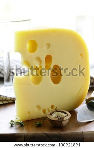 large piece of cheese varieties Maasdam on cutting board