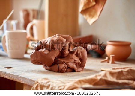 Large piece of red clay closeup on worktop at the potter workshop, close-up, shallow depth of field #1081202573