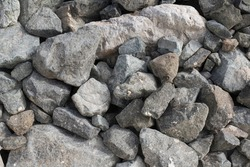 Large Pile of Grey Boulder Rocks. Stones for the construction industry. Stone background, dark gravel stone texture, granite.