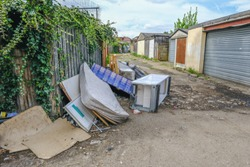 Large pile of rubbish, rotting after being fly tipped and left in an urban alleyway. Demonstrates anti-social behaviour.