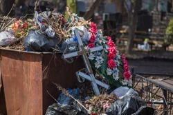 large piles of garbage among graves in old cemetery, people clean up trash from tombstones, a lot of dry branches from fallen trees, old wreaths, dried flowers, thrown crosses and temporary memorials