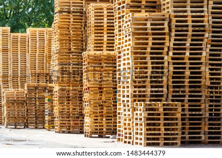 Large piles of pallets stacked outside on a sunny day