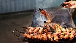 large pink shrimps langoustines with carapace lie on the grill with smoke. BBQ outdoor. Human hands are seen cooking over a fire.