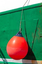large plastic orange buoy hanging from a ship attached to a rope