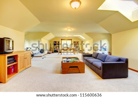Large play room with Tv, sport and games. Home interior, yellow walls and beige carpet. Very long bright room.