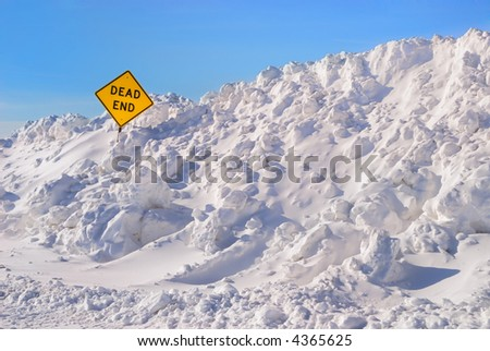 Large plowed snowbank surrounding a dead end sign