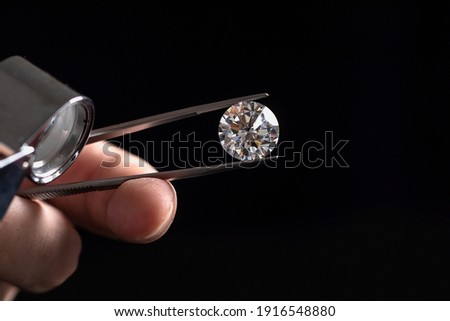 Large polished round cut diamond in hand close up front view. High quality photo