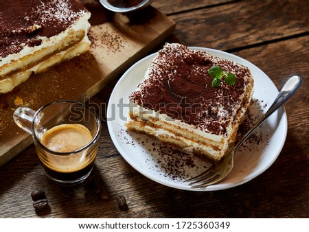 Large portion of fresh Italian tiramisu dessert served on a plate at table with espresso coffee alongside in a high angle view suitable for a menu Photo stock ©