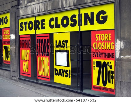 Large printed signs in a department store window announcing store closing and price reductions.