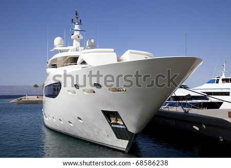 Large private luxury yacht moored in marina