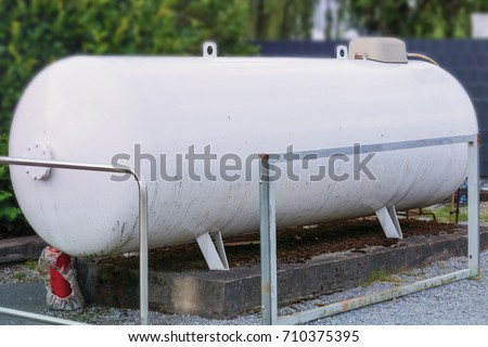 Large propane gas tank or liquid gas tank in a garden.