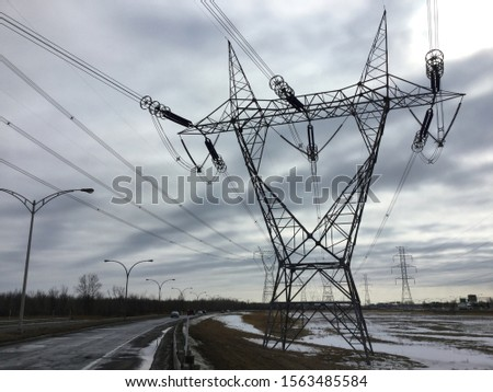 Large Pylons near a road in an electric winter landscape #1563485584