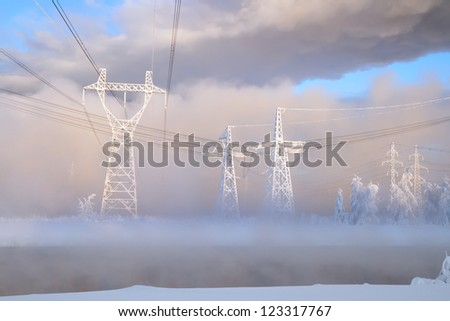 Large pylons of an electric main on a frost in the sun before sunset, Russia, Siberia