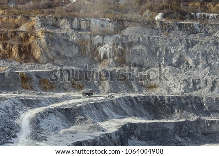 Large quarry dumper moving on the road in a limestone quarry against the background of a stepped terraced relief. Mining industry. Mine and quarry equipment. #1064004908