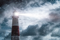 Large red and white lighthouse on a rain and storm filled night with a beam of light shining out to sea