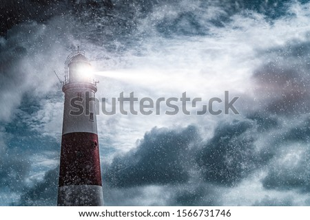 Photo of  Large red and white lighthouse on a rain and storm filled night with a beam of light shining out to sea