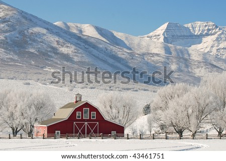 Large red barn in winter snow with tall mountains in the background.