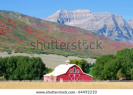 Large red barn with Timpanogos Mountain and the Wasatch mountain range in the background with autumn colors.