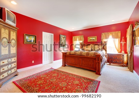 Large red bedroom with old bed and two windows.