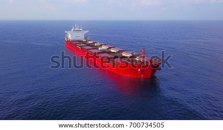 Large red bulk oil carrier ship sailing / docking in open ocean near large power station - aerial view