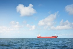 Large red cargo ship sailing in the North sea, Norway. Freight transportation, nautical wessel, global communications, logistics theme