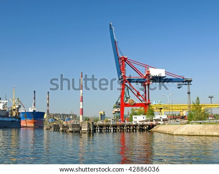 Large red container crane at an industrial harbor in Gdansk, Poland. - stock photo