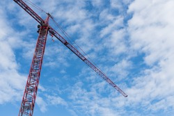 Large red crane at construction site in downtown Boston, Massachusetts. Construction crane on cloudy blue skies background