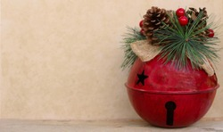 large red jingle bell decorated with pine cone, berries and raffia bow on a tan background with copy space