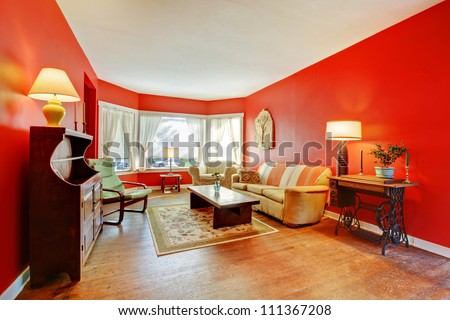 Large red living room with hardwood and antique furniture with lamps.