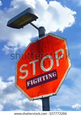 Large red road sign with the words Stop Fighting.