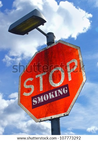 Large red road sign with the words Stop Smoking.