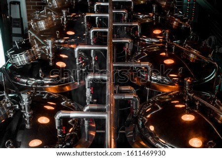 Large reservoirs, tanks and pipes with manometers in private microbrewery. Craft beer production line. Industrial interior background.  View from above. Foto stock ©