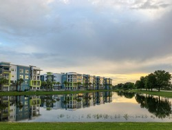 Large retention pond reflecting sky, trees, and apartment buildings on a cloudy evening in west central Florida, USA