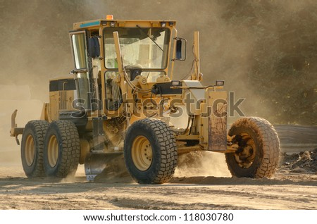 Large road grader working ground at a new commercial housing development