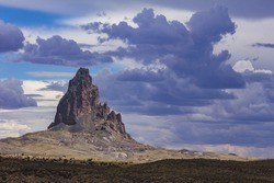 Large rock formation juts into the sky filled with clouds