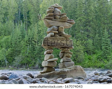 Large rocks stacked and balanced to form an Inuksuk stone landmark or cairn as a marker or monument in front of boreal forest taiga wilderness terrain