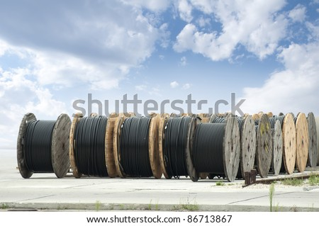 Large rolls of black cables on blue sky background